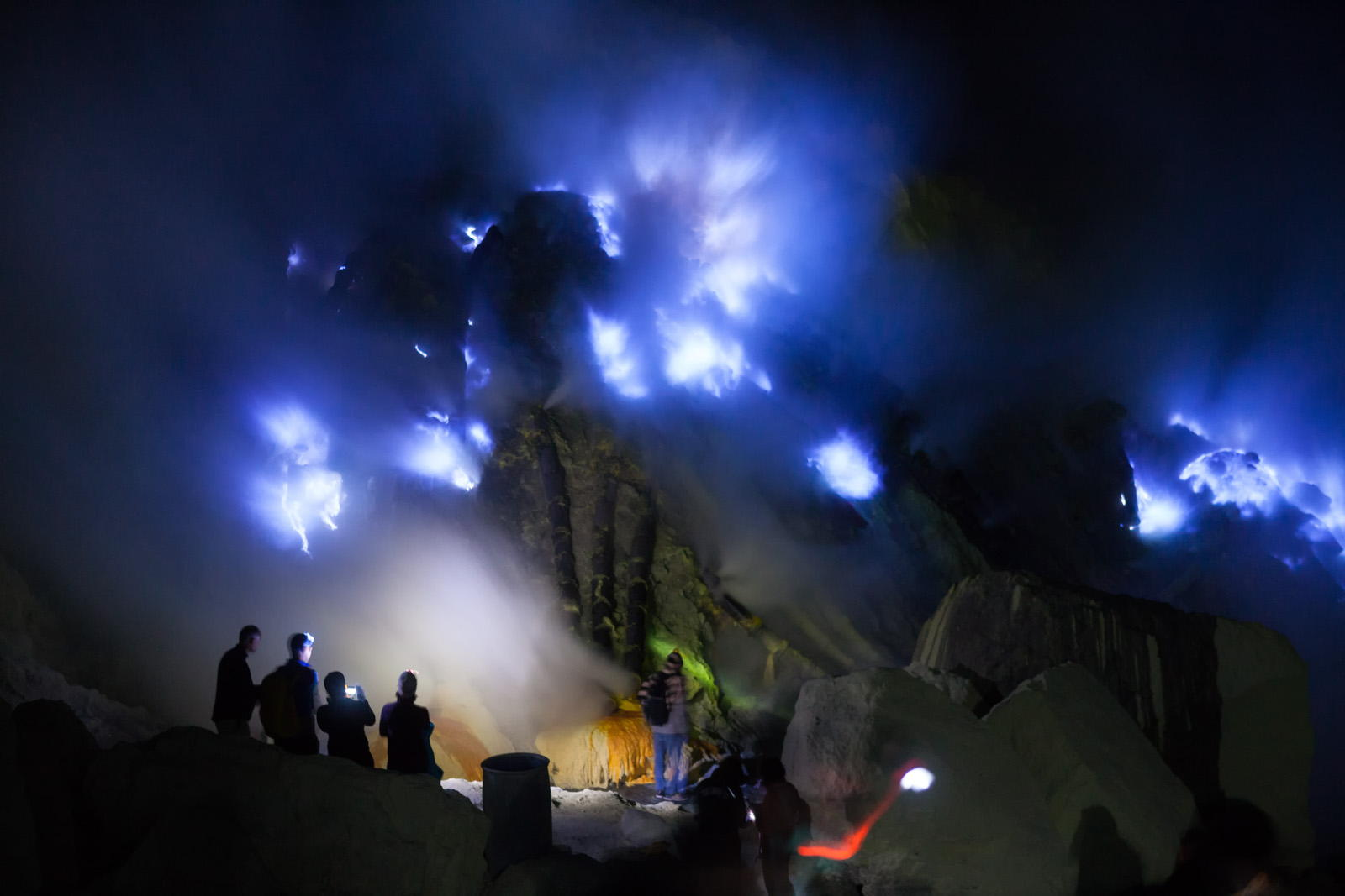Silhouette of tourists looking into the blue fire a flow of liquid sulfur which has caught fire and burns with an blue flame. Cater of the Kawah Ijen volcano, Java, Indonesia.